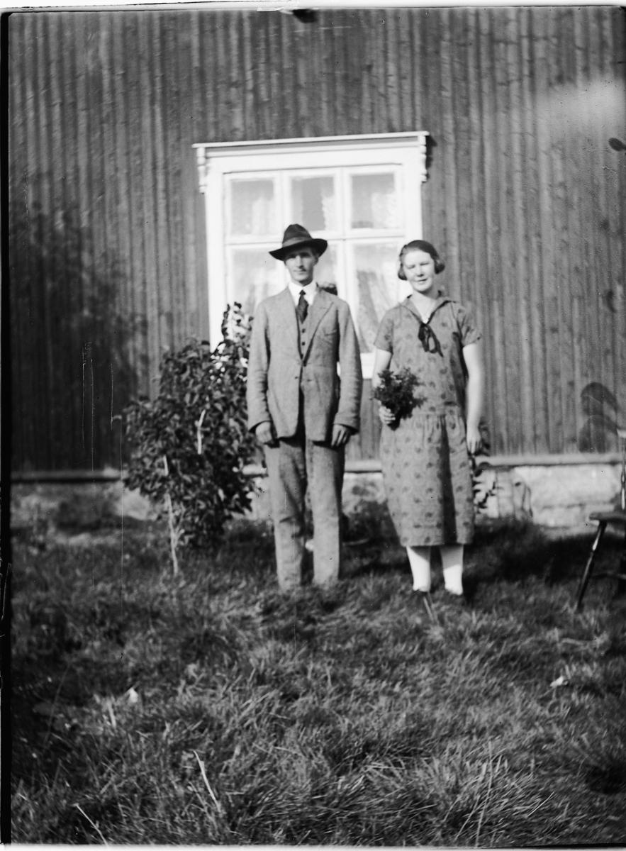 Ukjent mann og kvinne foran et ukjent hus. Hun holder blomster.