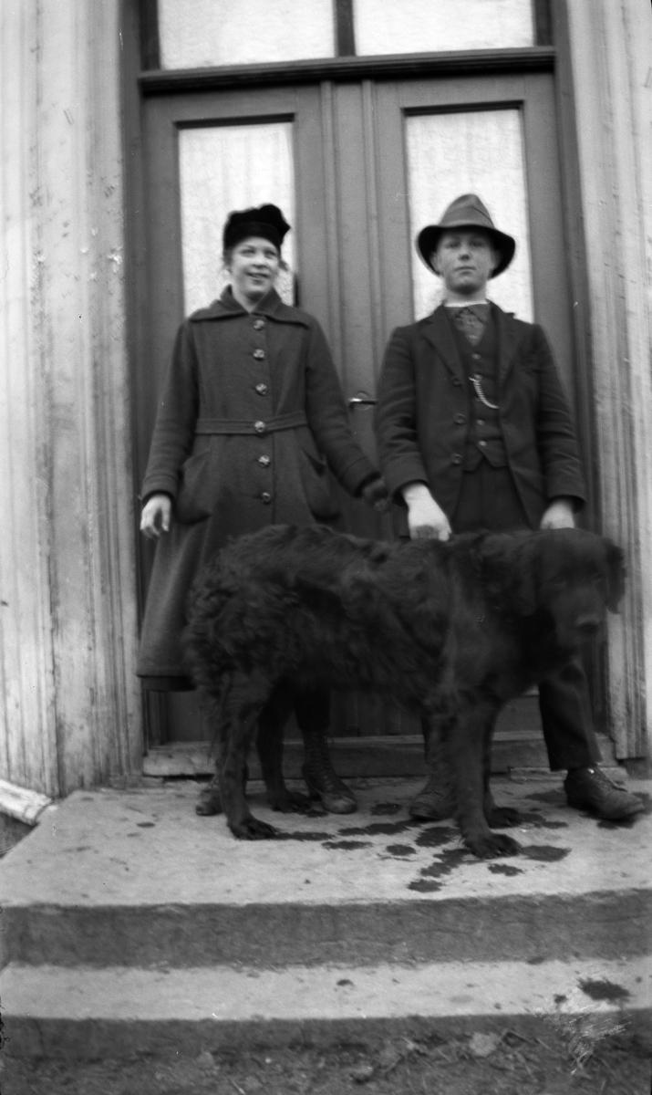 Ukjent gutt og jente med en hund på trappa ved inngangen til et hus.