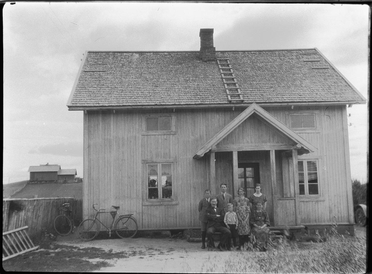 Ukjent familie ved inngangen til et hus. Sykler inntil husveggen.