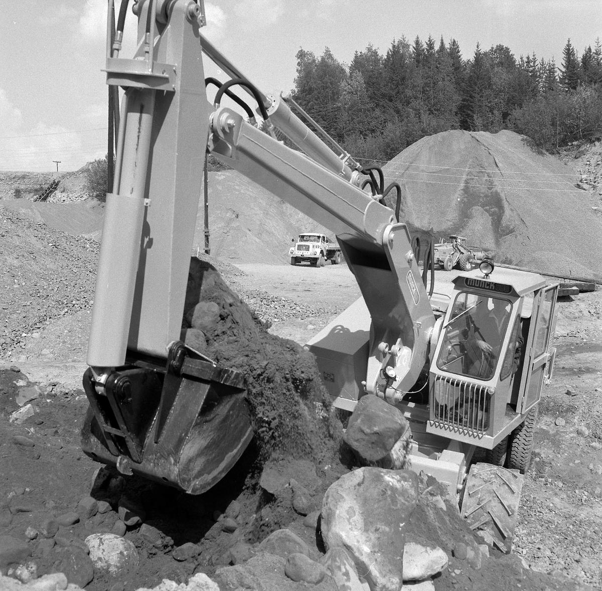 Munch gravemaskin. Maskinen har samme type understell som Brøyt. Jernhjul og gummihjul. Brøyt kunne hekte grabben på planet på en lastebil, og trekkes på gummihjulene. Den trengte ikke spesialtransport. På arbeidsstedet trakk den seg fram med grabben, men hadde også drift på jernhjulene.