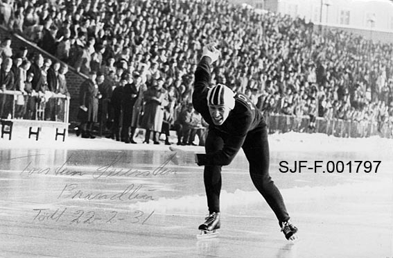 """Skøyteløperen Torstein Seiersten fra Brandbu på Hadeland, fotografert under et stevne på Bislett stadion i Oslo, antakelig i 1950-åra.  Seiersten er iført mørk, tettsittende trikot med """"NORGE"""" med kvite bokstaver på ryggen.  På hodet har han ei tettsittende, kvit skøytelue med flaggfargene - rødt, kvitt og blått - i striper på fronten.  På hendene har han kvite strikkevotter.  Løperen har et innbitt uttrykk i ansiktet, og han veiver med armene, antakelig for å drive opp farten mot slutten av et løp.  I bakgrunnen står publikum tett på tribuner bak et nettinggjerde.  Over den lyse isflata i forgrunnen til venstre har noen skrevet """"Torstein Seiersten, Brandbu, Født 22-2-31"""" med grønn kulepenn."""