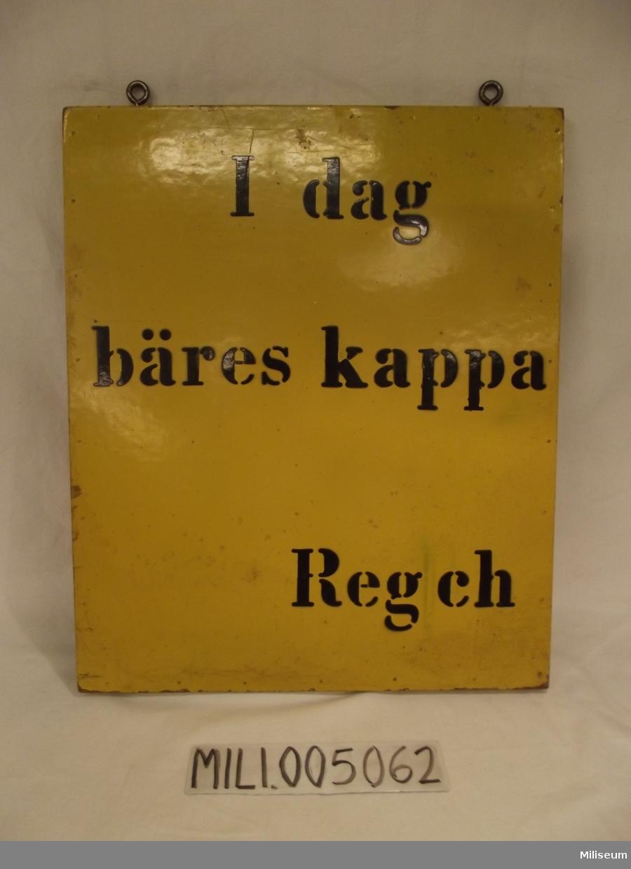 """Skylt: """"I dag bäres kappa, Regch""""."""