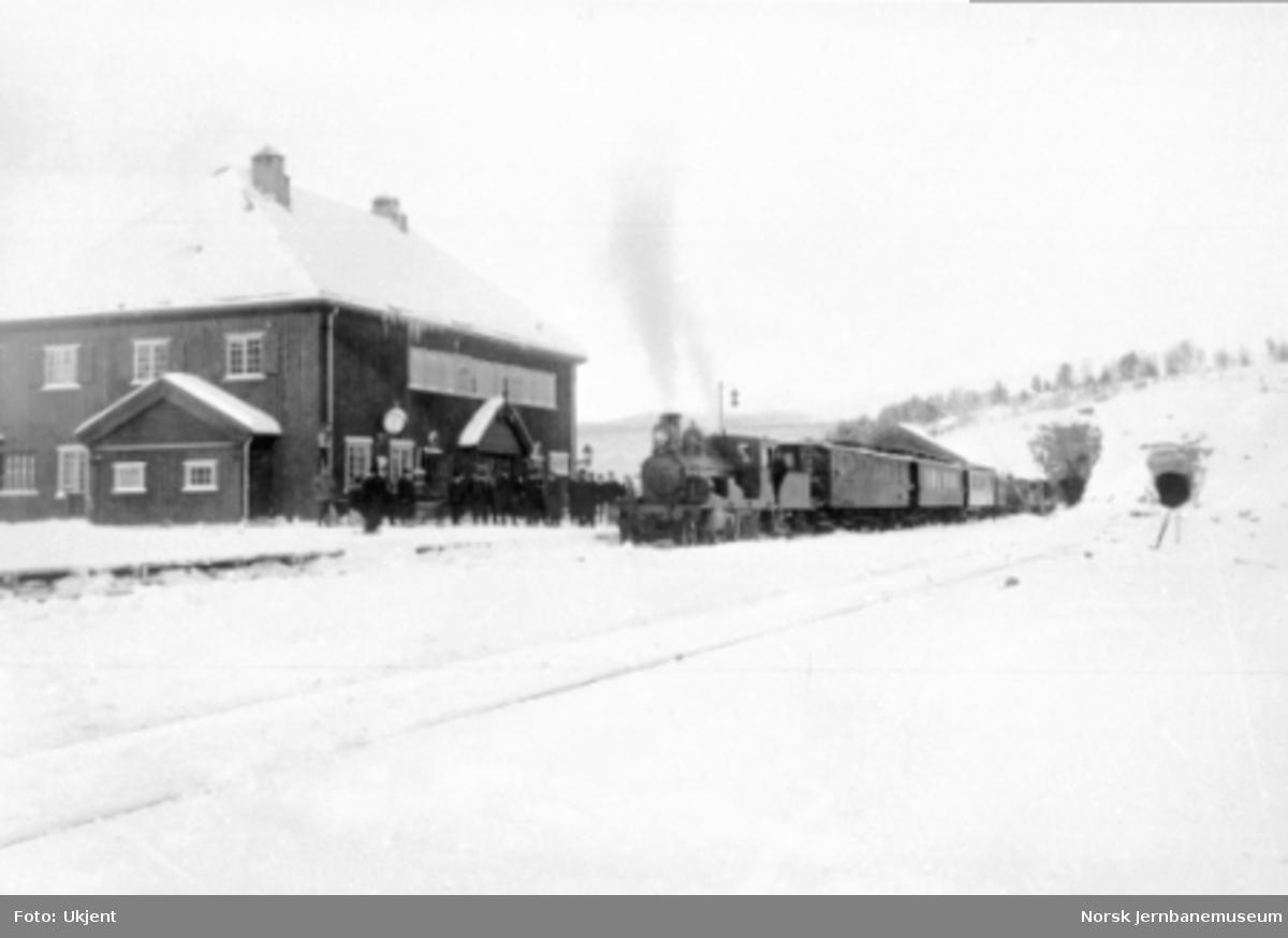 Vinterbilde fra Dombås stasjon med damplokomotiv av type 13a med persontog i spor 1