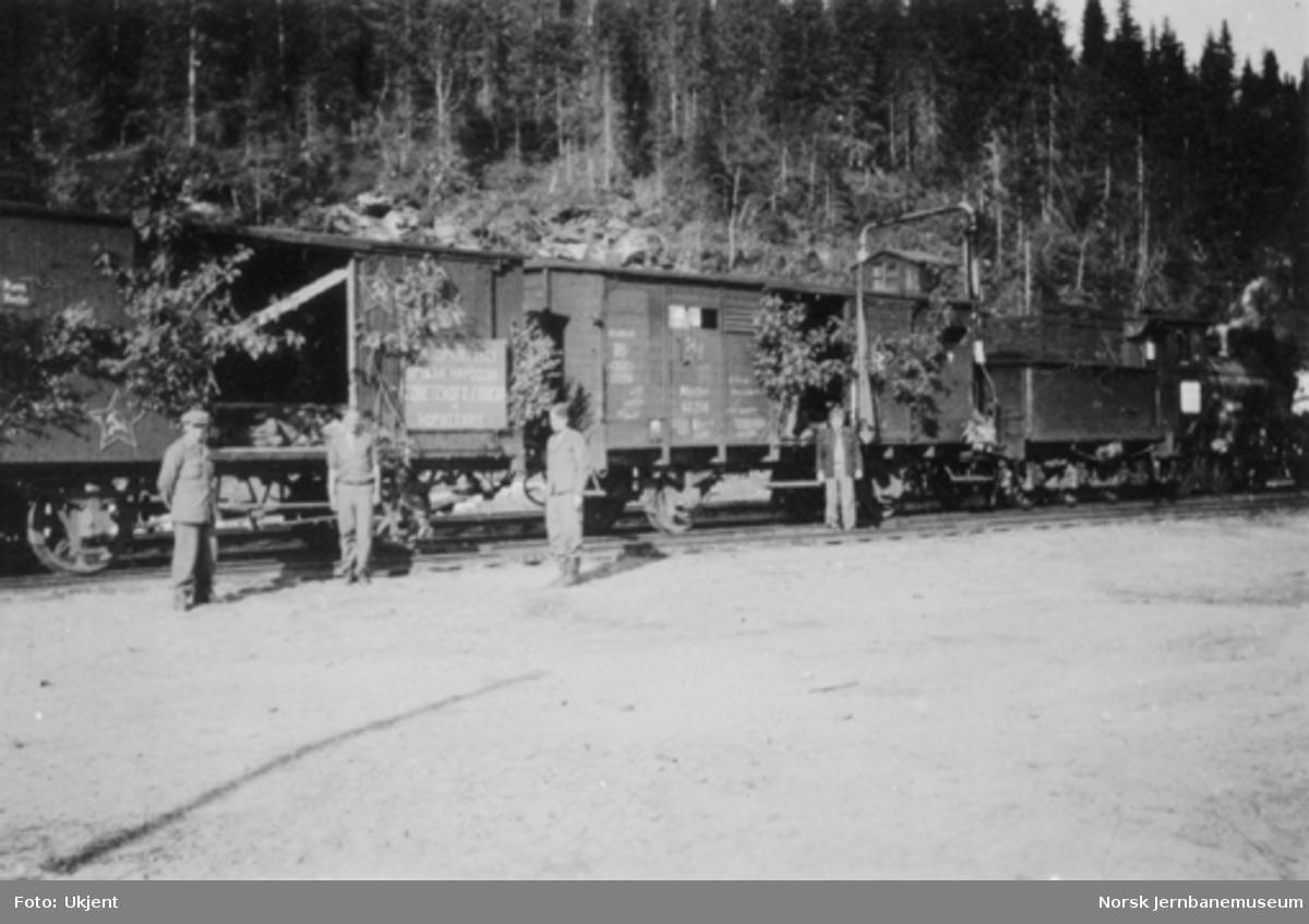 Russiske krigsfanger i godsvogner pyntet med bjørkekvister, hammer og sigd samt en russisk plakat