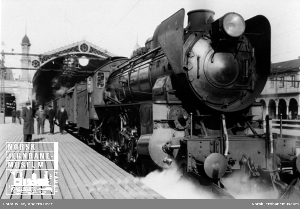 Damplokomotiv type 31b nr. 451 foran tog på Oslo Ø med stasjonshallen i bakgrunnen