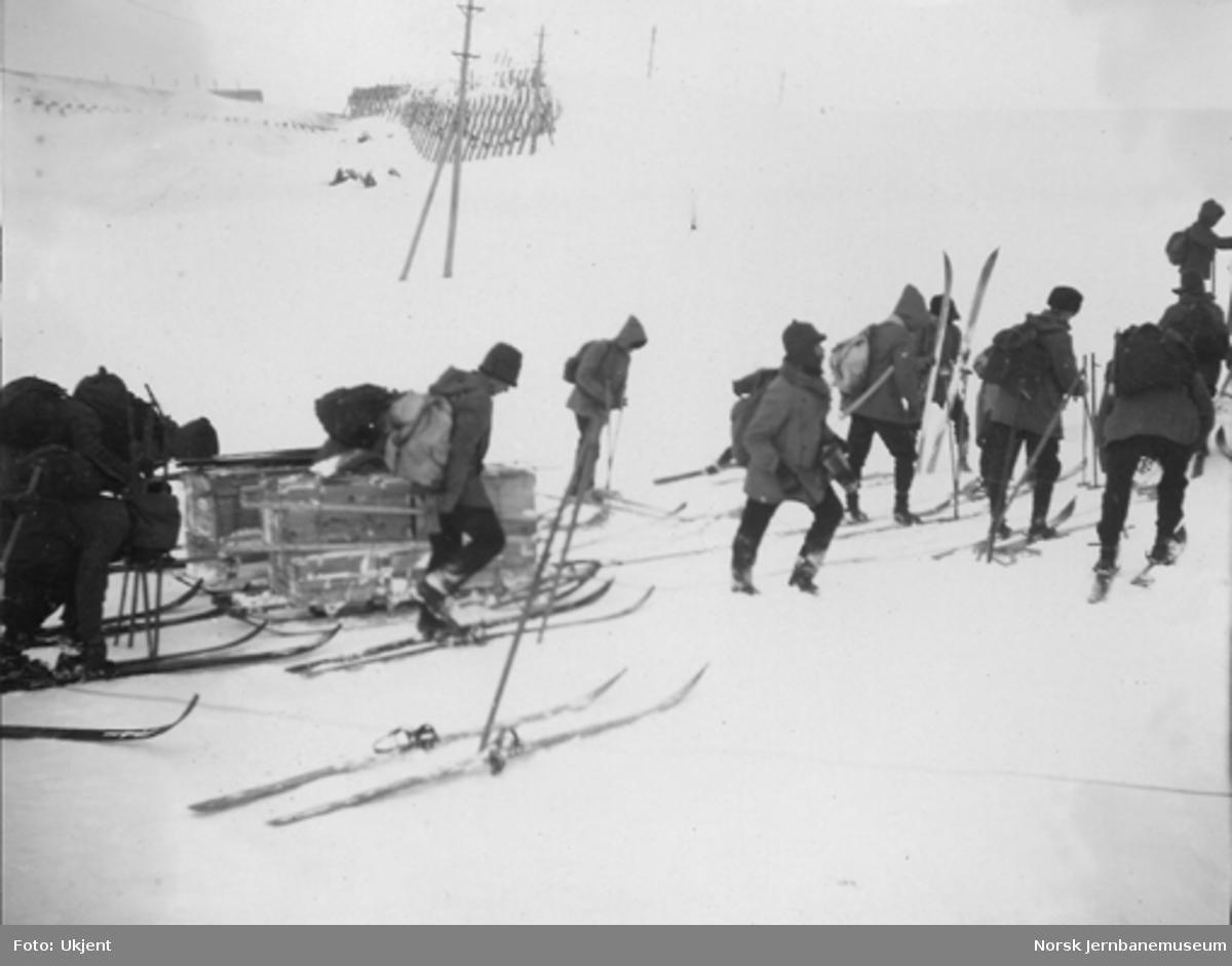Snøblokade; menn på ski med diverse utstyr