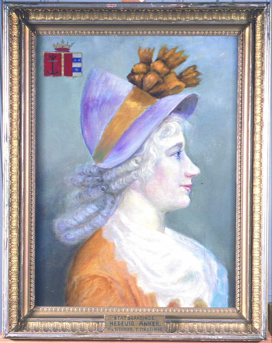 Kvinneportrett, profil. Hedevig Anker. Gul-orange kjole og sjal i et tynt, hvitt stoff. Fiolett hatt med bånd i samme farge som kjolen. Grått hår, antagelig pudret, ikke parykk. Våpenskjold i øvre venstre hjørne.