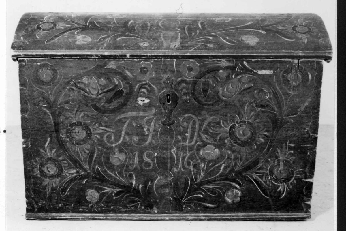 Kiste med buet lokk, brunmalt med blomsterdekor. Blåmalte tverrbånd. Innvendig i lokket slitt rosemaling.