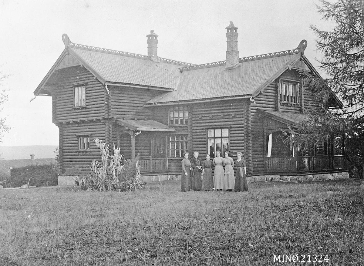 Kvinner oppstilt foran stor villa