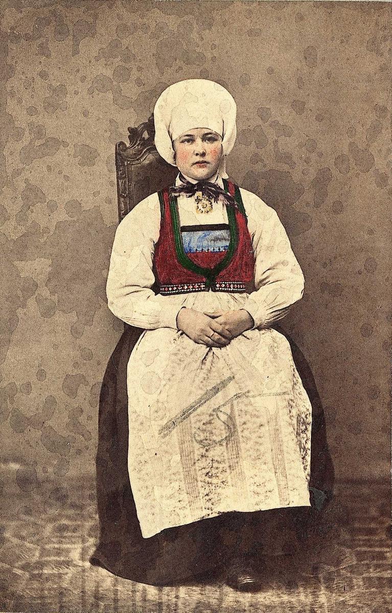 """32. Konedrakt fra Kvam, Hordaland. Portrett av kone sittende på høyrygget stol i fotoatelier med nøytral bakgrunn og mønstret gulvteppe. Håndkolorert. Fra serien """"Norske Nationaldragter"""" (nr.32), fotografert av fotograf Marcus Selmer (1819-1900), Bergen."""