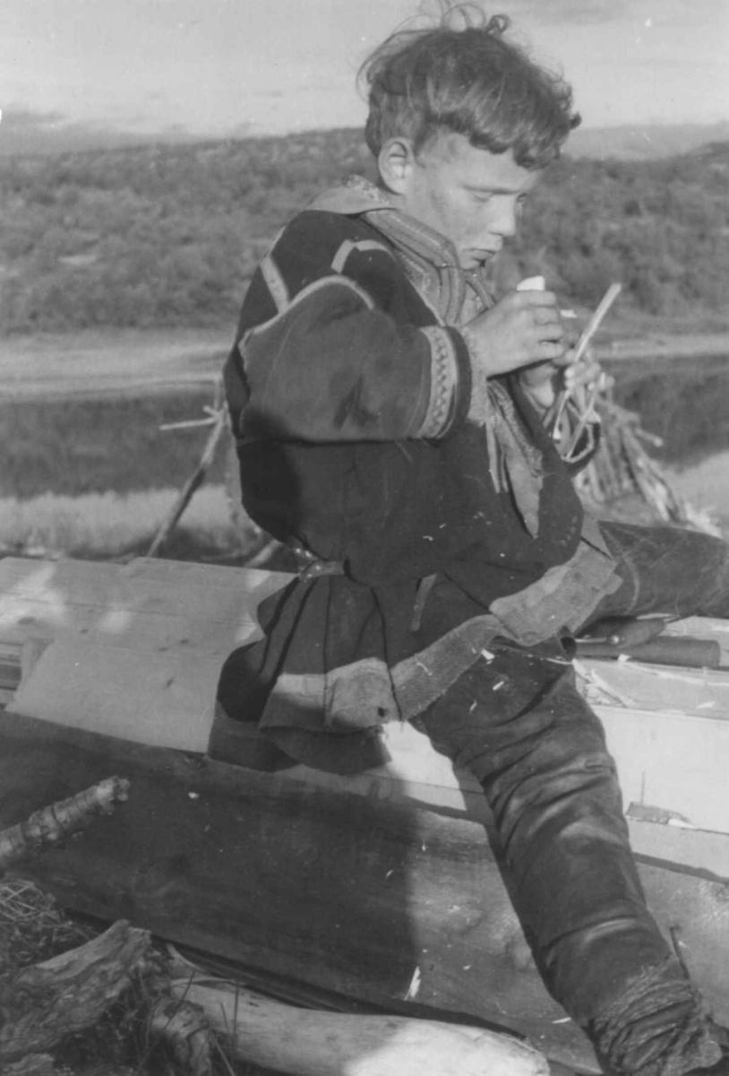 Per Mikkel Utsi sitter på en plankestabel og lager flymaskin. Hemmujavve 1953.