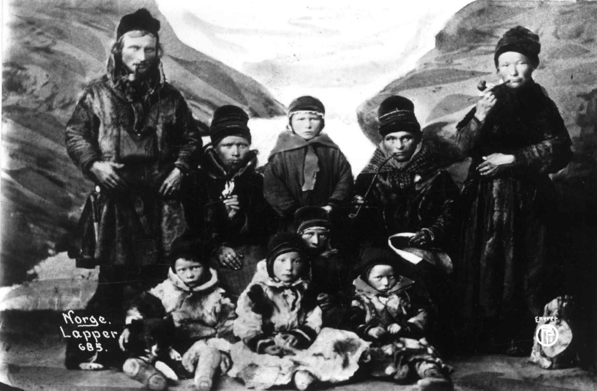 Svenske samer. Fire voksne med piper og seks barn. Malt naturlandskap i bakgrunnen. Karesuando.