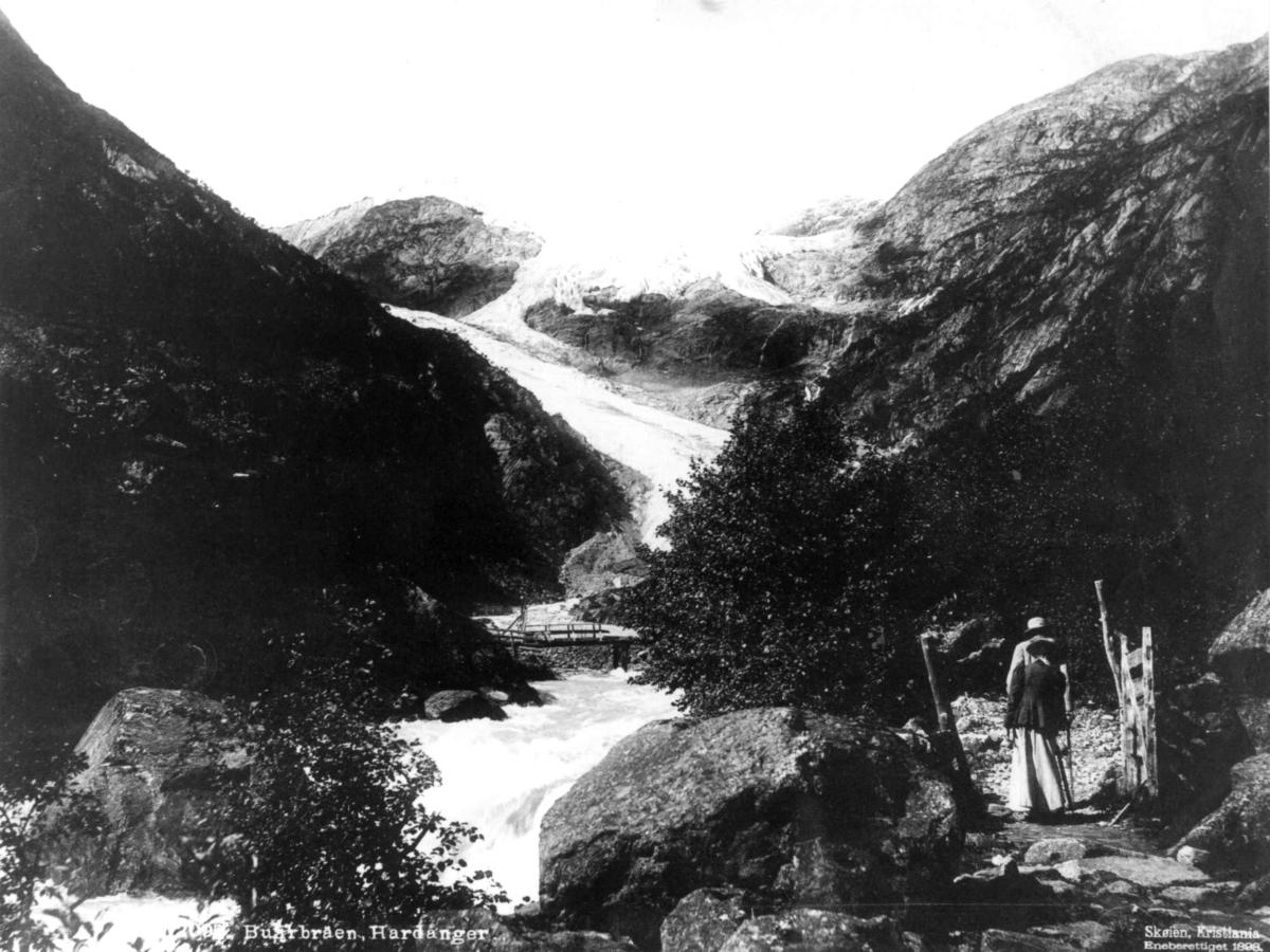 Buarbreen, Odda, Hordaland. Personer ved grind i forgrunnen.
