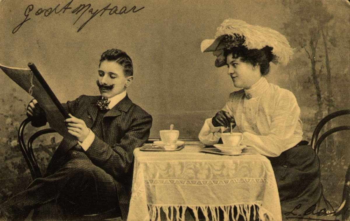 Postkort. Nyttårshilsen. En kvinne og en mann sitter ved et bord og drikker kaffe.  Han leser for henne. Stemplet 20.12.1904