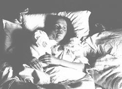 Kvinne i sengen med spedbarn. Mor Margrethe Q. Wiborg og lil