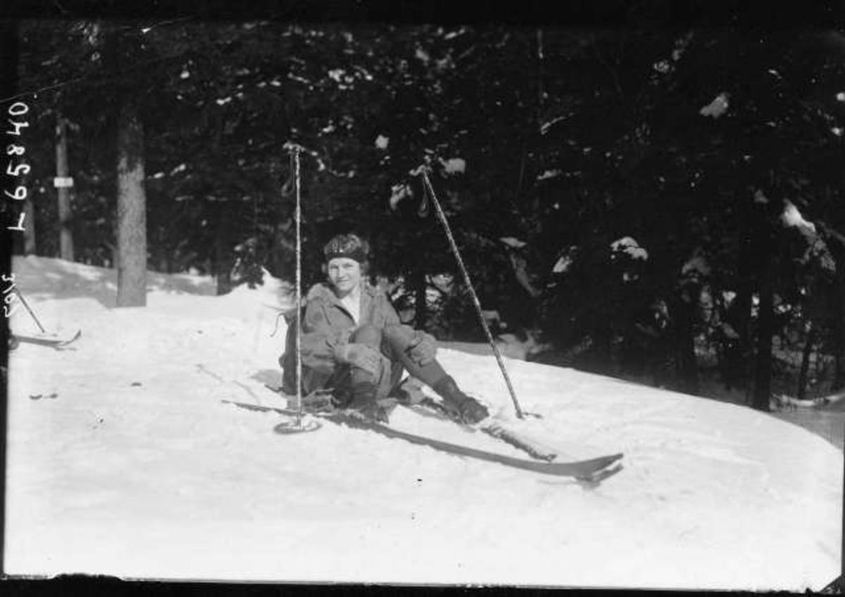Kvinnelig skiløper har pause, sitter i snøen.