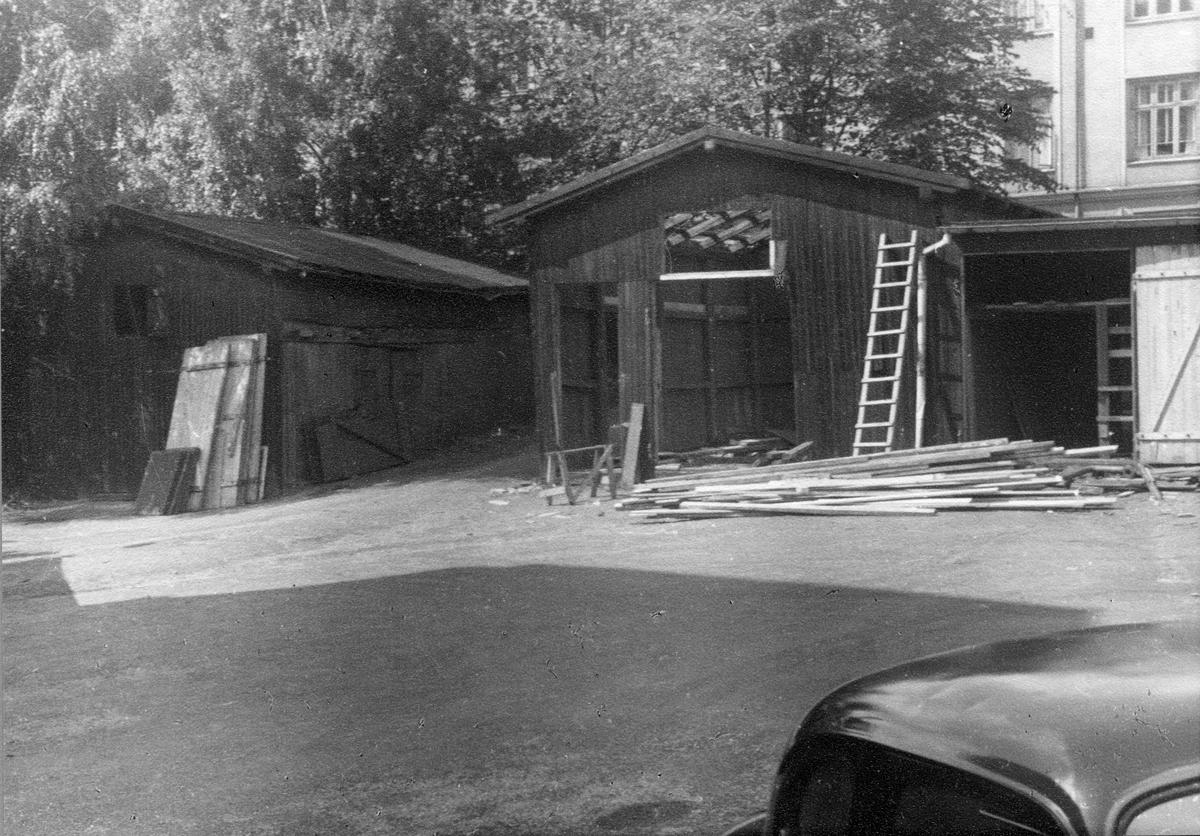 Gamle lagerskur på tomten til Holbergsgate 1 i 1954. Foto fra byggearbeider foretatt ved J. L. Tiedemanns Tobaksfabrik fra sommeren 1951 frem til høsten 1955.