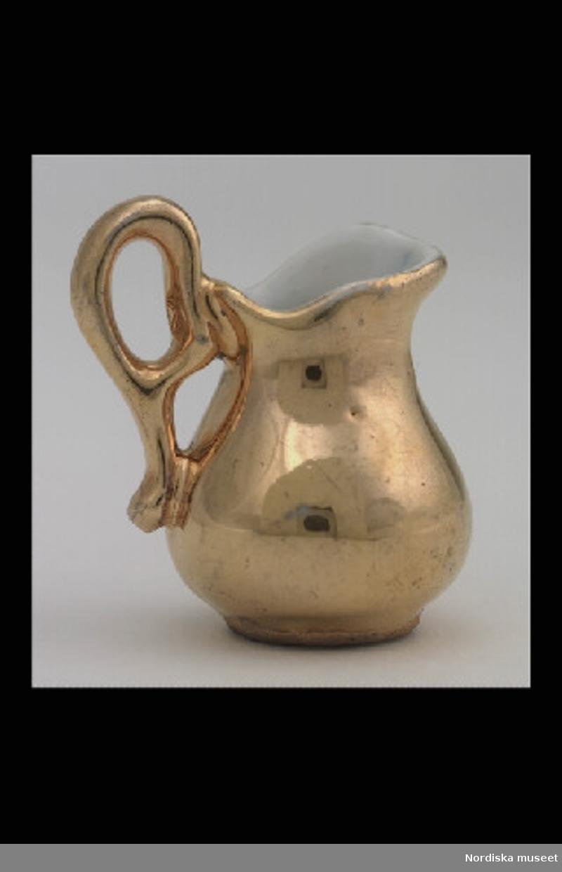 Inventering Sesam 1996-1999: H  kaffekanna  4,5 (cm) Kaffeservis (a-g), till dockskåp, av vitt porslin, utvändigt helt förgylld, rund, bukig form med uppsvängda hänklar. Kaffekanna (a) med lock (b), hänkel saknas Sockerskål (c) med lock (d), en hänkel saknas, locket trasigt Gräddkanna (e) 2 koppar (f:1, g:1) och 2 fat (f:2, g:2) Tillhör dockskåp inv.nr 193.059. Skåpet och dess möbler är ritade 1880 av givarinnans far som lät en snickare tillverka dem. Anna Womack okt 1997