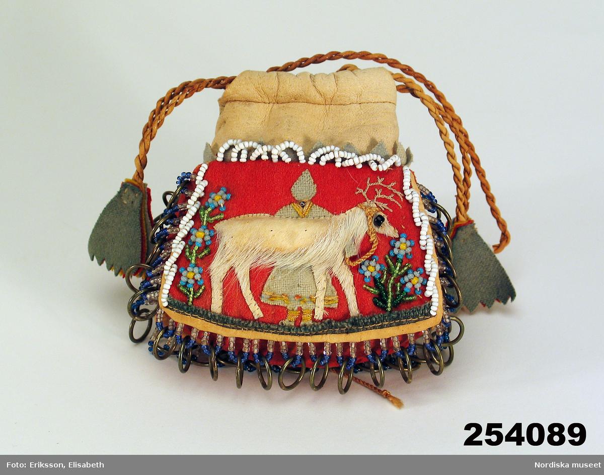 """Huvudliggaren: """"Skinnpung, turistslöjd, ofärgad skinnöverdel med tofsförsedd dragsnodd av tvinnat skinn, nederdel invändigt fodrad med tyg, utvändigt botten och sidor av rött skinn, ena sidan har en ren av skinn med hår och lappkvinna samt blommor av glaspärlor, andra sidan en lappkåta och glaspärlsblommor på tygbotten. I[nköpt] 11/3 1957 [från] Fru Maja Wickboms dödsbo gm major O. Wickbom, Stockholm jämte 254.083 - 098 [...]. [Brukningsort:] Jämtland."""""""