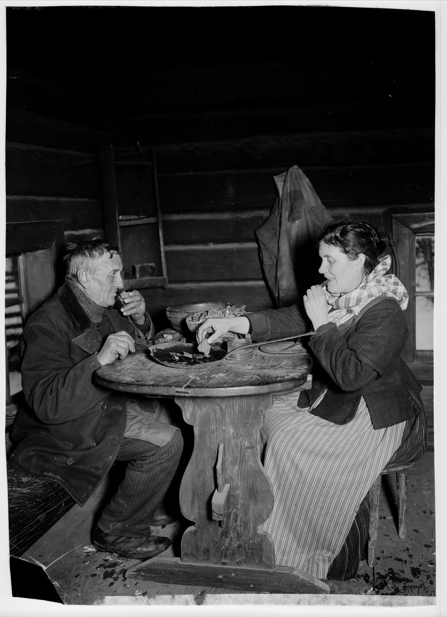 Spisning av nävgröt och stekt fläsk i en värmländsk-finsk rökstuga. Grötbitarna doppas i fläskpannan, och för varje munsbit gröt bites ett stycke av fläsket, som hålles i andra handen. Bakom pannan står grötkoppen och längst bak på bordet ett svarvat träfat med mjölk att njuta till efterrätt.