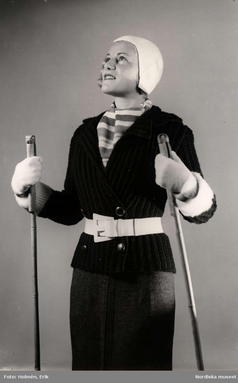 """""""Stickat"""", kvinnlig modell med en stickad kofta, vantar, mössa och halsduk. Hon håller ett par skidstavar i händerna. Varuhuset Nordiska Kompaniet i Stockholm visar vintermode 1936."""