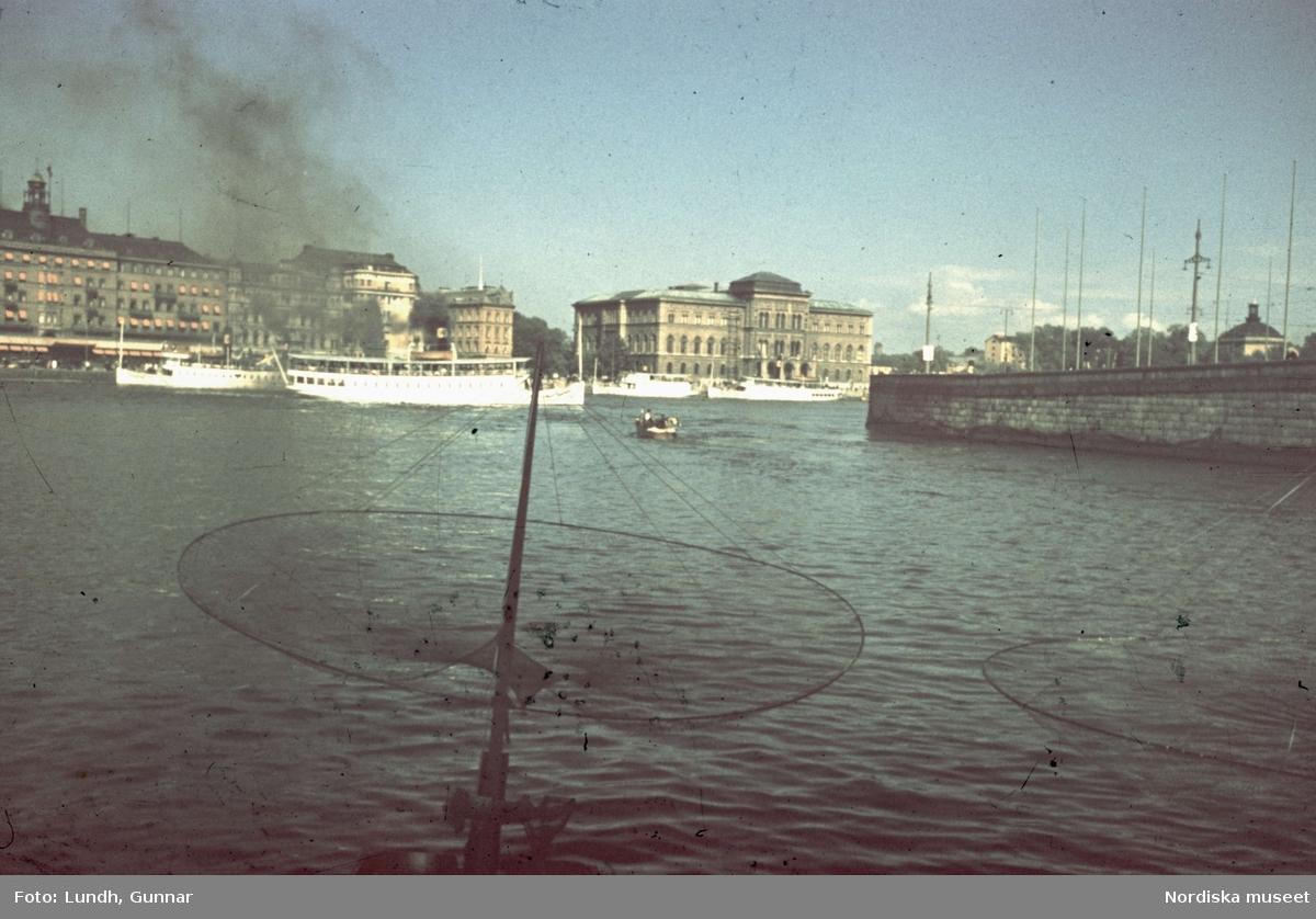 En håv till en liten fiskebåt vid Stockholms ström. I bakgrunden flera skärgårdsbåtar och Blasieholmen med Nationalmuseum. Utsikt från Strömparterren.