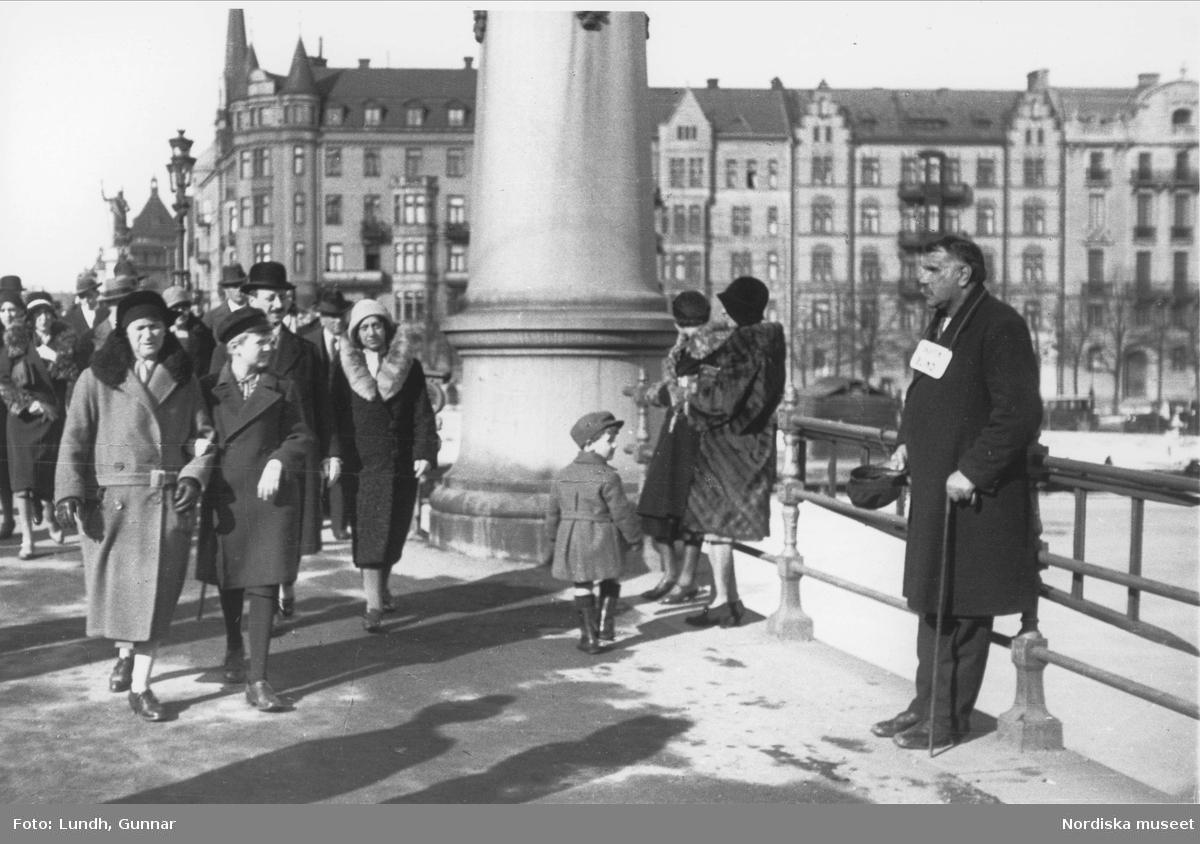 """Blind tiggare på Djurgårdsbron med en skylt om halsen med texten """"skjuten blind"""", välklädda människor passerar, Strandvägen i fonden. Stockholm."""