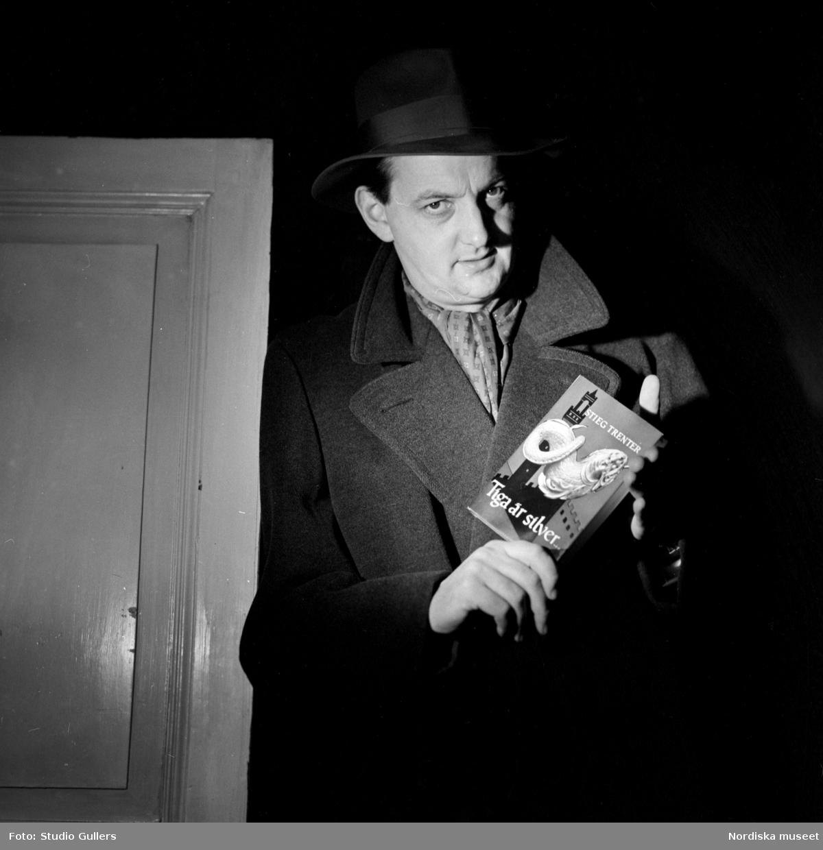 """Fotografen K W Gullers med ett exemplar av Stieg Trenters deckarroman """"Tiga är silver"""". Gullers var förebildens till bokens huvudperson Harry Friberg."""