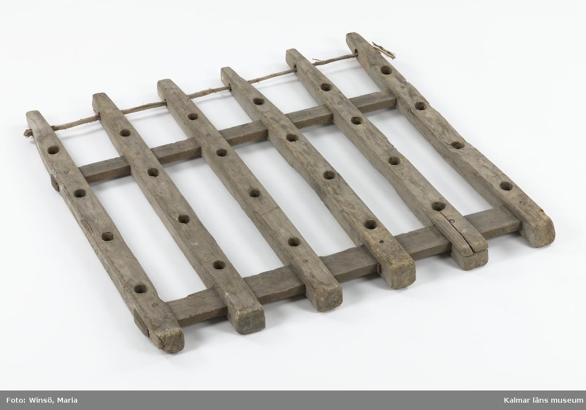 KLM 24148. Harv, pinnharv, del av, trä. Den ena delen av en tvådelad pinnharv. Ramverk av trä bestående av sex stolpar med två tvärgående slåar. Varje stolpe har fem runda hål för träpinnar. Hela harven består av en likadan del och kopplades samman med hjäp av vidja som är trädd genom hålen i harvens ena ände. Kan höra samman med KLM 24149, KLM 24150 eller KLM 45224. Pinnarna som hör till harven kan finnas bland KLM 45225 (Pinne, harvpinne).