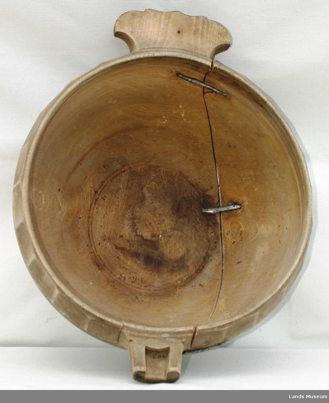 Rund bolle med tut og og håndtak formet som et lite øre. Bord med enkel forsenkninger øverst langs kanten. Trøysen er sprukket i to, men er naglet sammen med jernnagler.