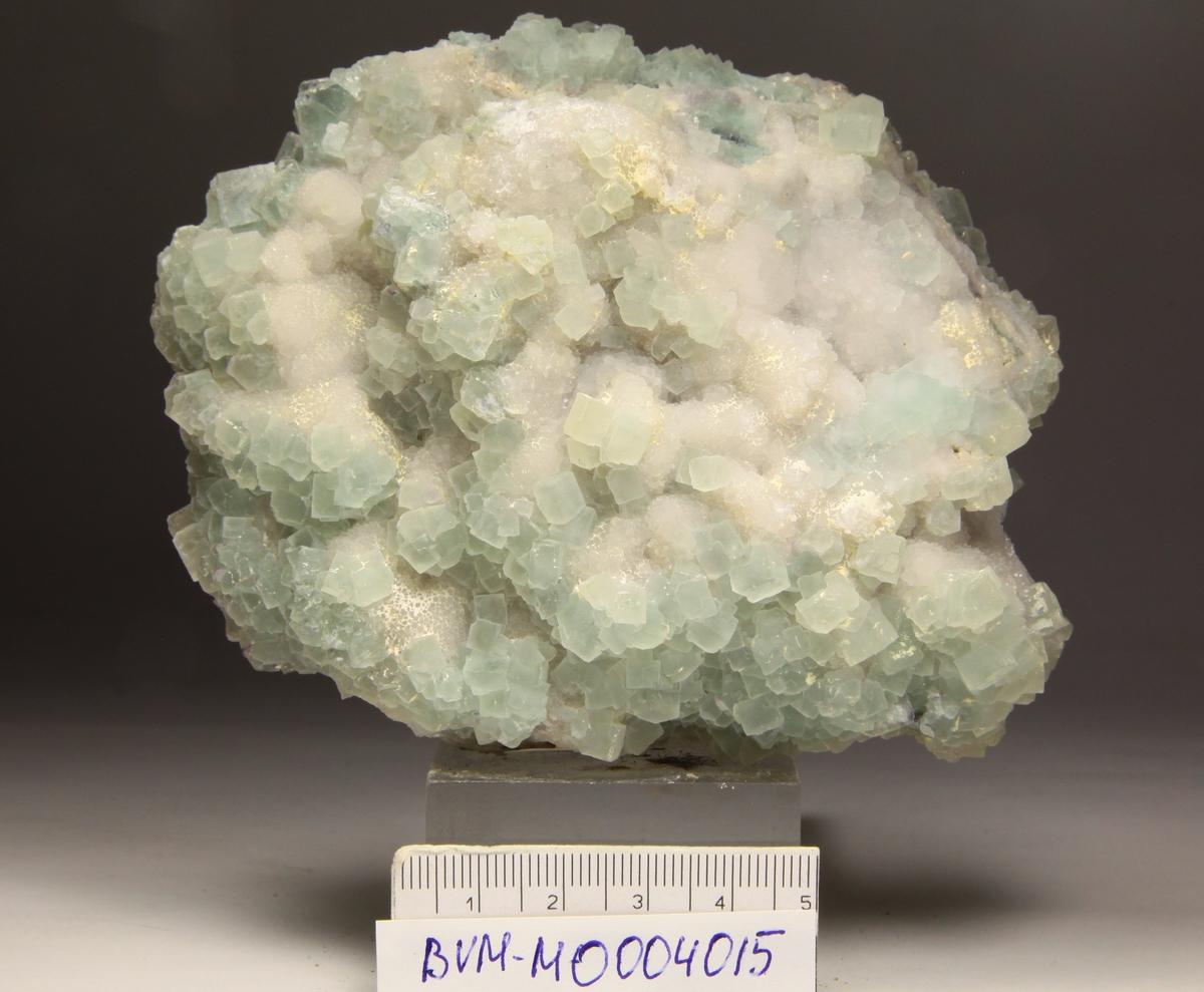Flusspatgruppe, blekgrønn. Krystaller også på baksiden, små krystaller på kvarts. Kube med kantflater, med krystallvekst på kubeflatene.