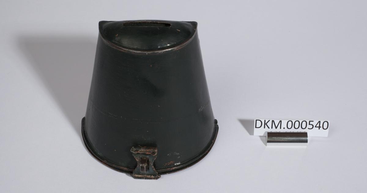 Sparebøssen er formet som en skrå, halv sylinder. Den er bredest nederst å smalner oppover. Baksiden er flat slik at bøssen kan henges på en vegg. Topp og bunn er flate halvsirkler. Den har en sprekk til å putte i penger på toppen og kan åpnes i bunnen.