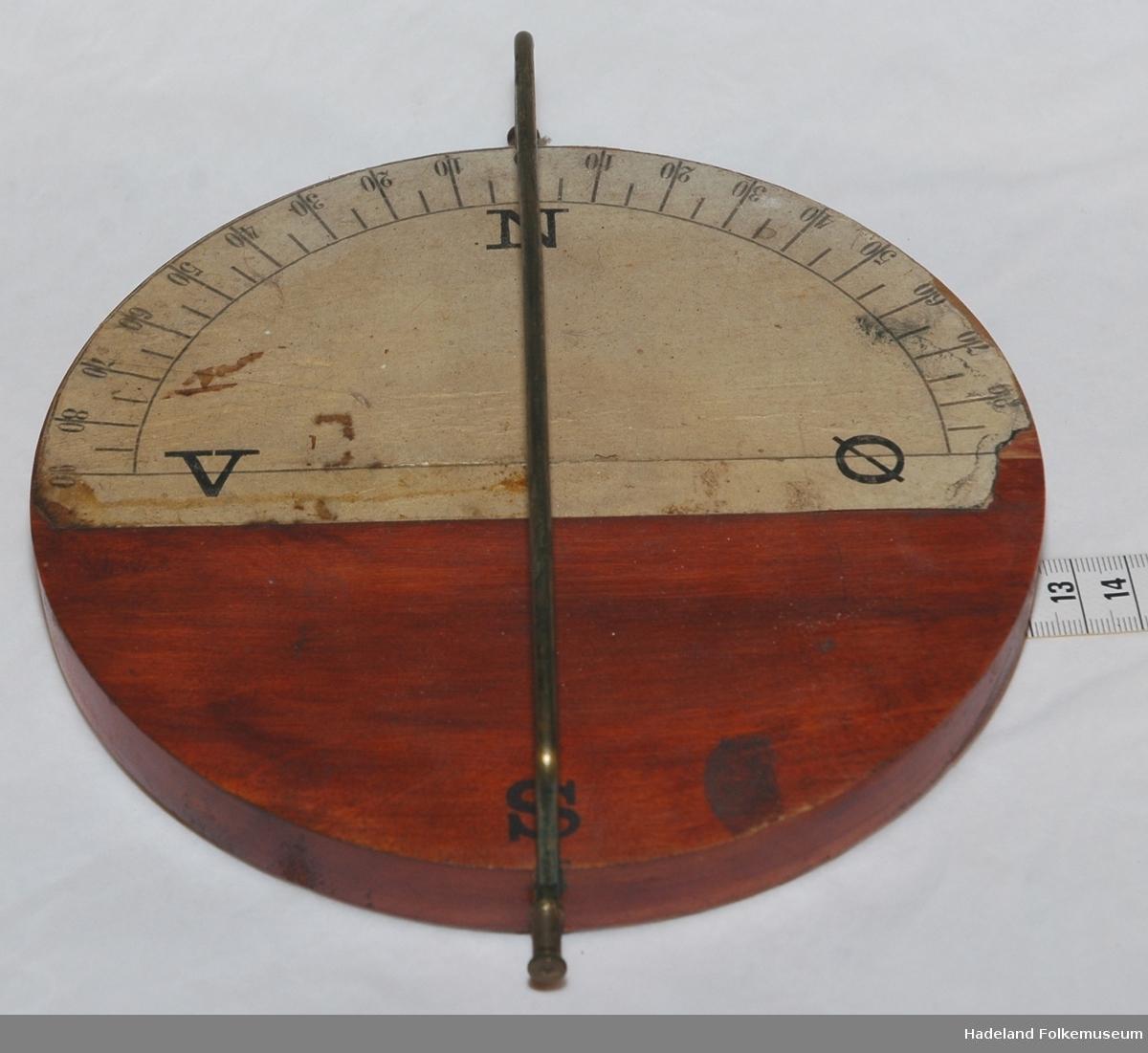 Rund treplate. Kompassnål mangler. Messingtråder fra N til S og ender i hver sin skrue til å feste ledninger.