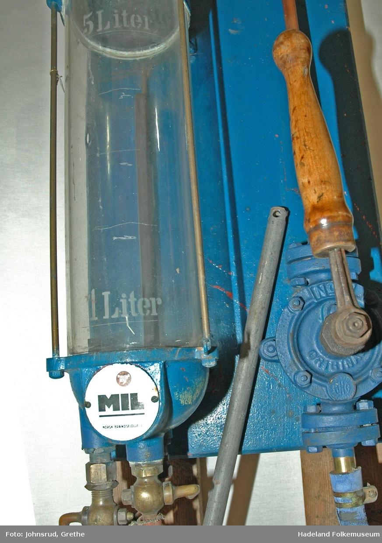 Pumpe montert på rektangulær treramme. Sylinderformet glassbeholder med tappekran og dreneringskran neders. Under beholderen er et trebrett til å sette kanne eller lignende på ved tapping.