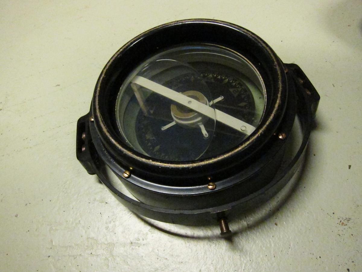 Sortlakkert kompass som kan betraktes fra begge sider.