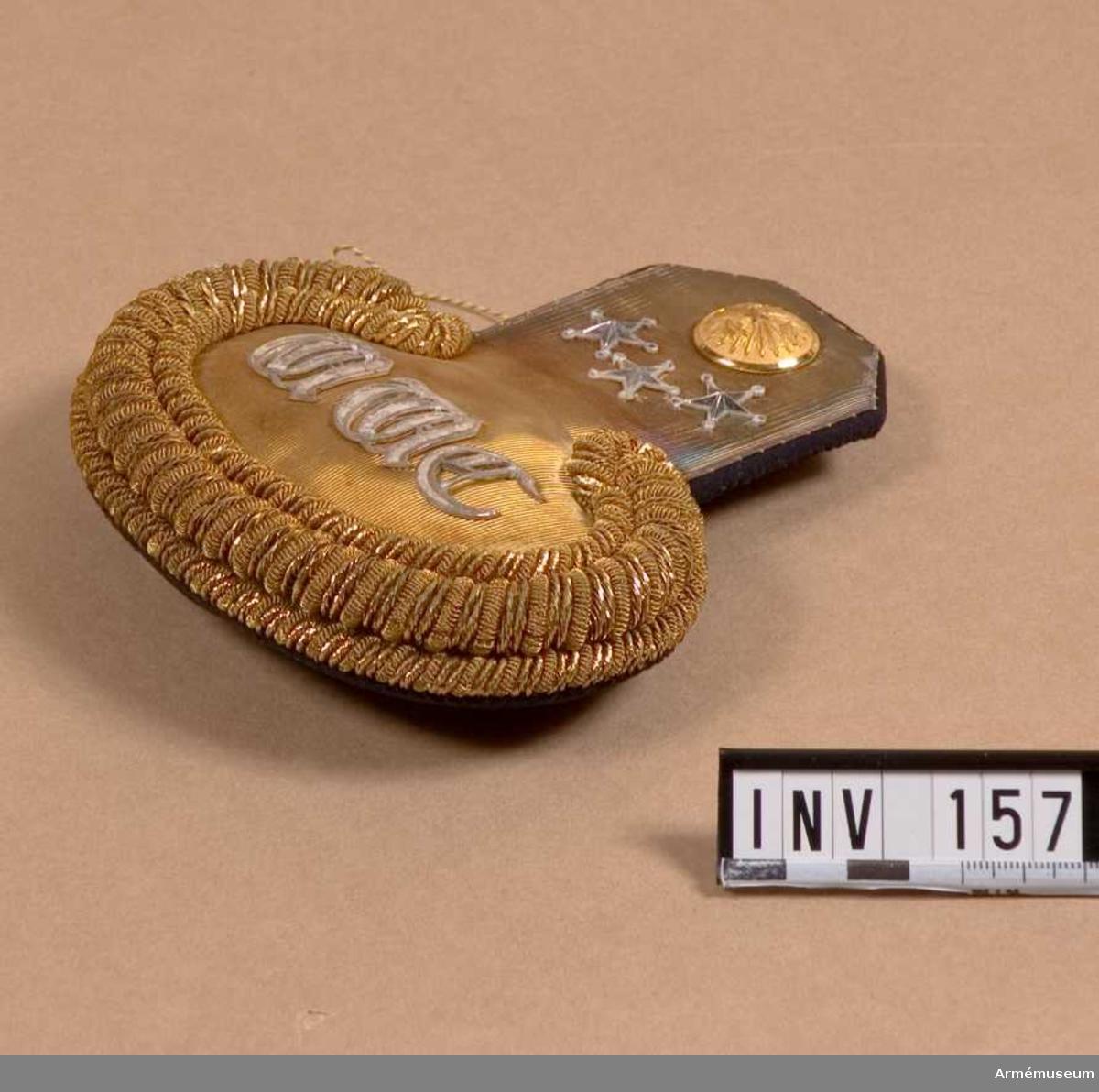 Matta av slät guldgalon, med silverbokstäver: W W C. Liggande  guldgalon runt yttre epåletten, 3 varv. Fodrad med blått kläde. Haken i metall märkt: Militärekiperingsaktiebolaget. Guldknapp  m/1886 för V o V byggnadskåren.  Tre st silverstjärnor = kapten. Längd 150 mm, bredd vid halsen 60 mm, stb vid ärmen 130 mm. Vänster.