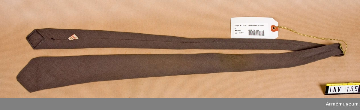 Slips tillverkad av ljusare gråbrungrönt ylletyg med sned skärning och dubbelvikt.
