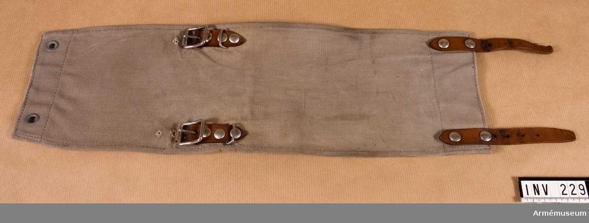 Damasken är sydd i gråbrungrön smärting. På kortsidornas insidor skinnskodd. Läderremmar, 120 mm långa, två st. Två spännen för damaskens fastsättning kring nedre delen av byxbenet och övre delen av marsch-skon.  Samhörande nr är 209-238 (220-238).