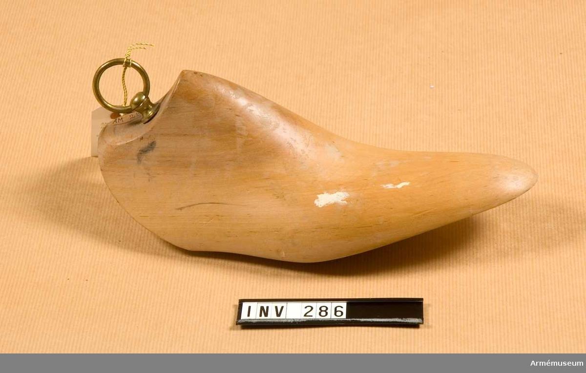 Blocket är format efter kängan i ett stycke trä. Försedd med dragring, diameter 30 mm, sittande i en ringhållare på skaft. Märkt H i sin övre del, synligt när blocket sitter i kängan.