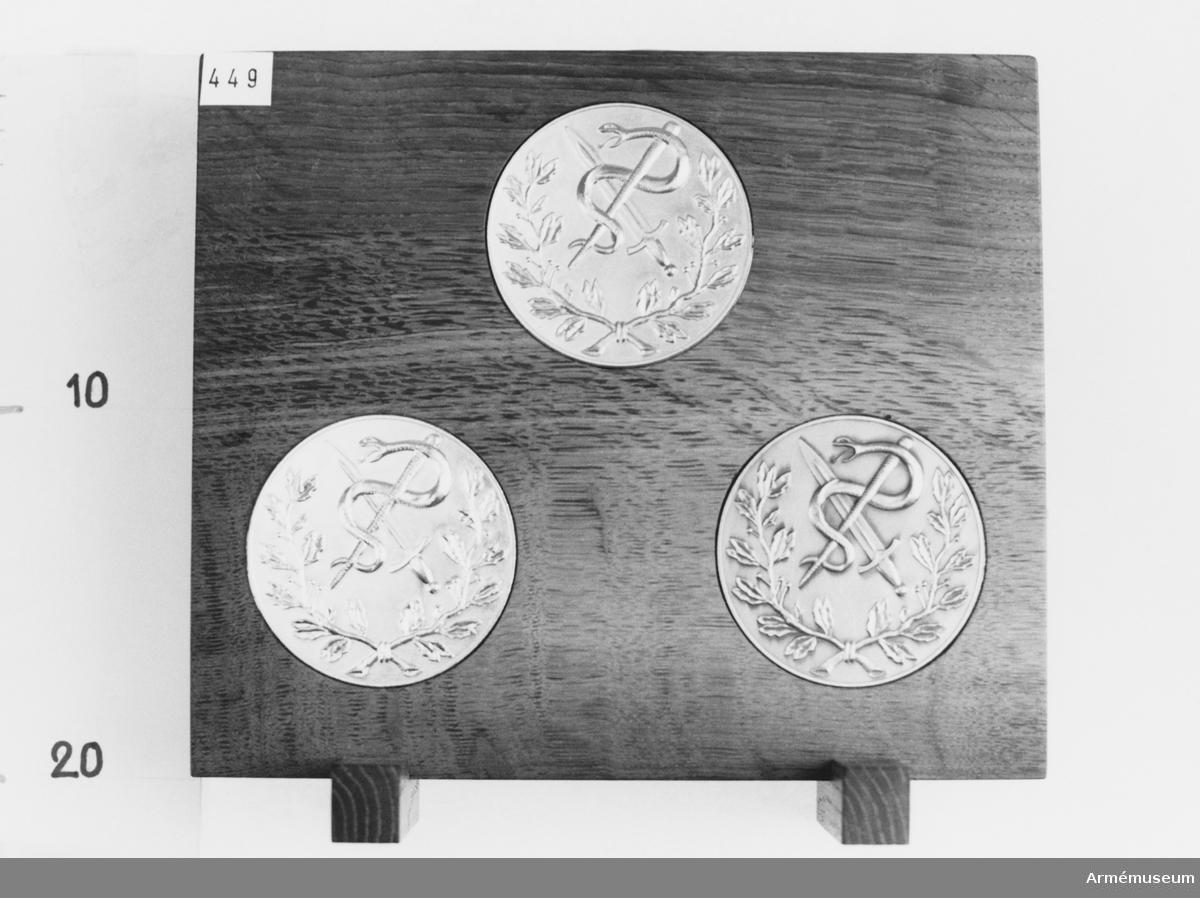 Placerade i medaljställ tillverkat av bröderna Sylvéen i Stockholm. Tvärställda fötter.  Medaljernas åtsida visar lagerblad omgivande försvarets medicinalkårs emblem; orm och stav lagd på kniv.   Frånsidan med inskription.