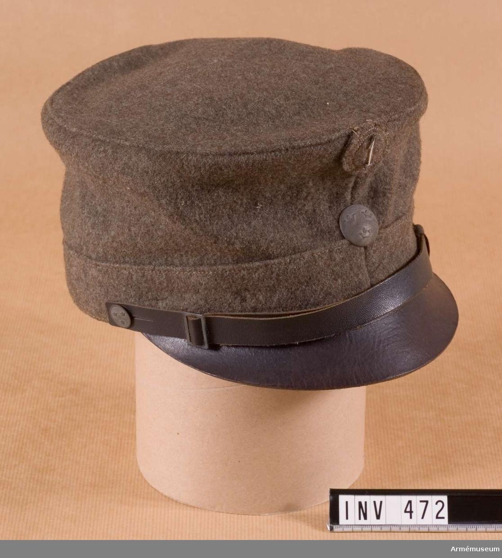 """Stl 58. I grå kommisskläde m/1923 med svart läderskärm och  hakrem. Mössknapp m/1923 med tre öppna kronor. Grå och något  kupad. Mössremsknapp m/1923, liten, med tre öppna kronor. Grå  och platt. Kompanimärke m/1923, vit, arabisk etta i metall. Kullen är 110 mm hög, med söm mitt fram och bak. En påstickad kant runt kullen, 35 mm hög, med söm mitt fram. Invändigt brun  lädersvettrem. Stöd för kullen i form av överklädda korsettstöd  i svart, stödjande ståltråd runt kullens insida. Grått foder med  tryckt stämpel i fyrkant: """"I 13 1926  58""""."""