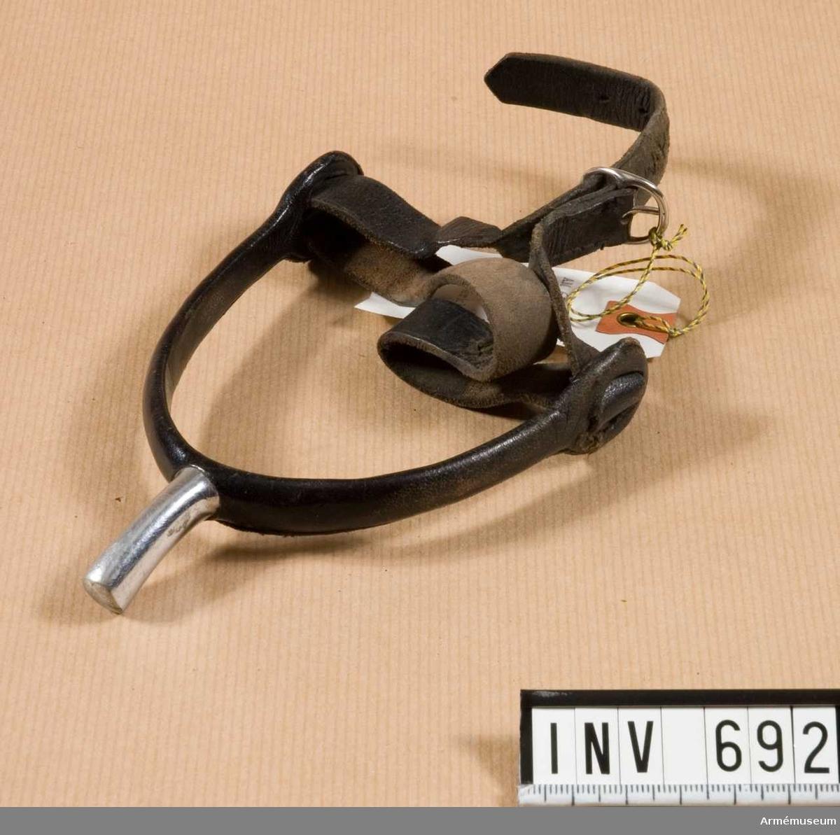 Av rostfritt stål utan trissor. Den hästskoformade delen är överklädd med läder (lädermaterialet hindrar stålet från att leda kylan). En enkel 10 mm bred svart läderrem håller sporren på plats.
