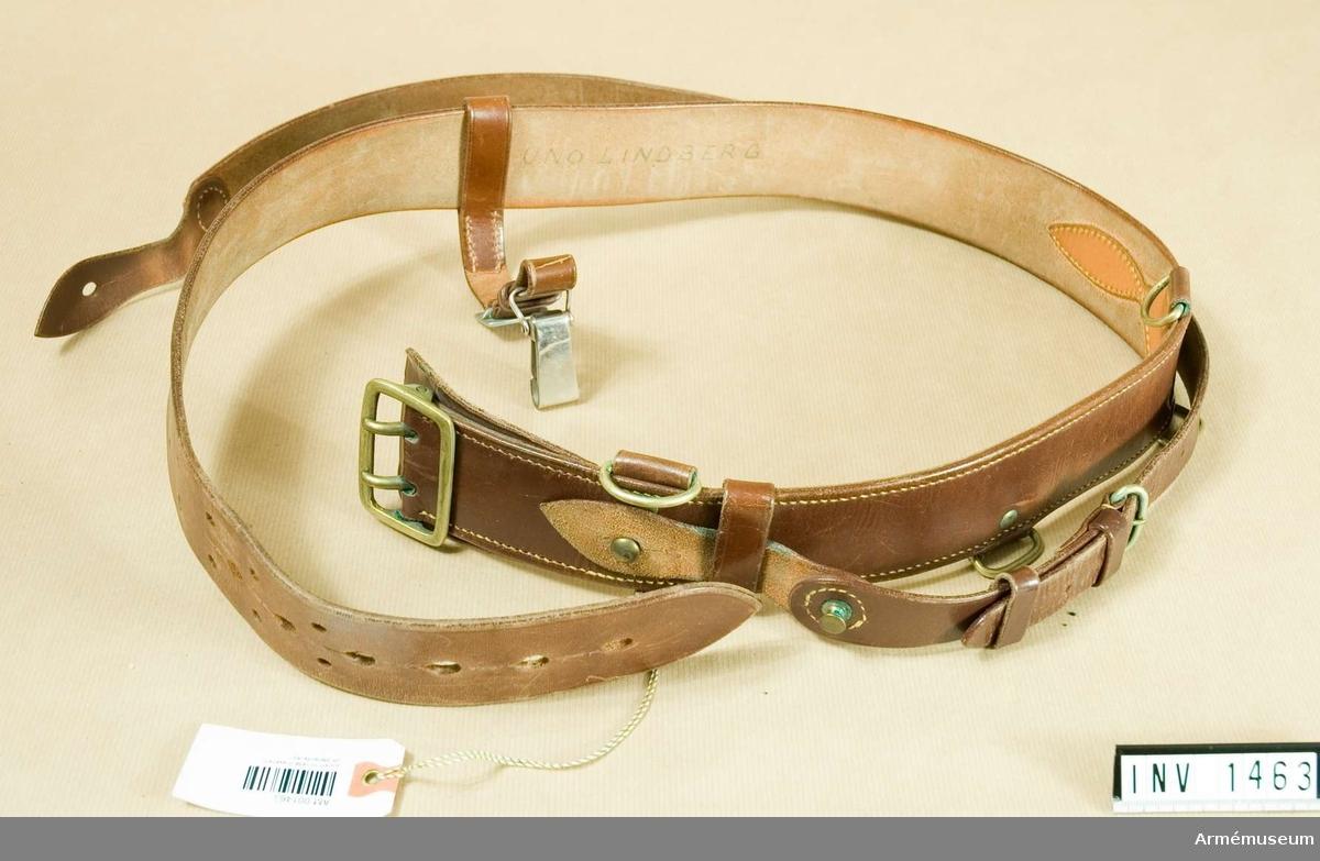 """Samhörande nr är 1454-1473.Livrem m/1939 m axelrem, officer.Av brunt läder. Spänne med två torn och ringar av bronsfärgad metall. För fastsättning av remmens ände finns en kraftig knopp och sölja. Tre st ringar på remmens nederkant för fasthäktning av tillbehör. Remmen är genomdragen en bärrem för sabel. På övre kanten är axelremmen fästad vid två ringar, vänster sida. Axelremmen skall vila över höger axel. Textat på avigsidan """"Uno Lindberg""""."""