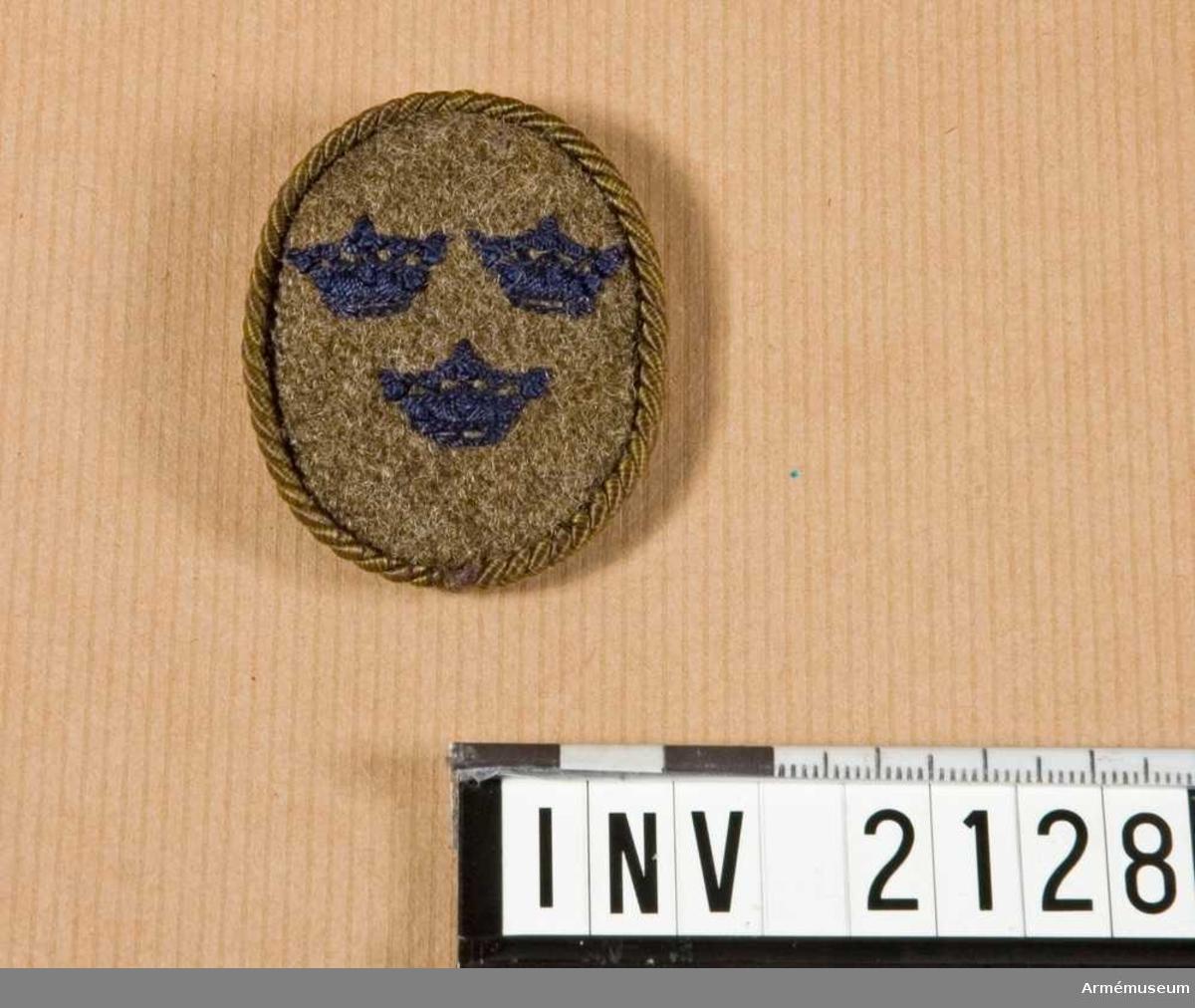 Samhörande nr är 2125-2129.Märke, t mössa, Landstormen.Av grågrönt kommisskläde i oval form, uppspänd på pappskiva. Broderad med mörkblå kronor, två och en. Omgiven av silkesnodd i  samma färg som klädet. På baksidan spänt bomullstyg, svart. Skall fästas framtill på mössan. Använd av M Öbergs svärfar E H  D Petersson som till 1918 var plutonchef för Stockholms södra  landstormsområde nr 45.