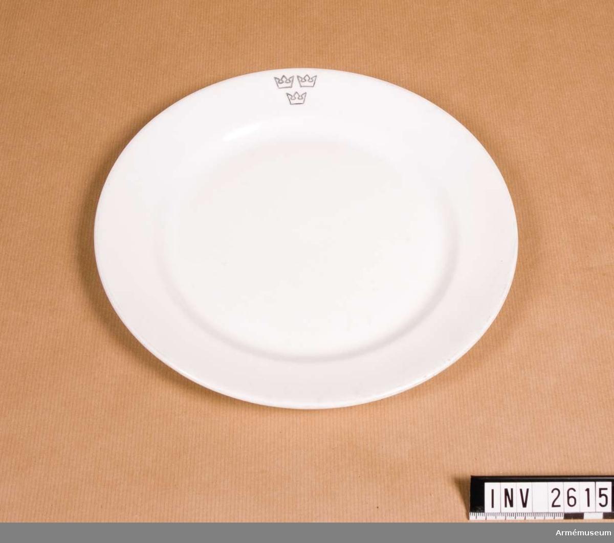 Vit med svart kronmärkning. Märkt i botten. Kronporslin använt vid matinrättningar på förband.  Samhörande nr är 2600-2615 (2608-2615).