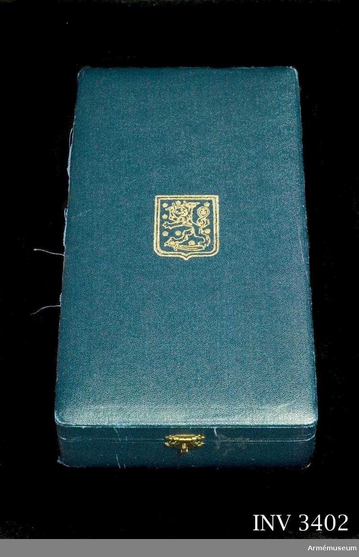 Mått: 240 x 130 x 50 mm.Ask till kraschan, storkors och band, Finlands vita ros' orden. Av blå klot med på locket i guld, riksvapnet, det  svärdsvingande pansarklädda lejonet. I locket står i guld  juvelerarens namn: A. Tillander.På en sammetsskiva vilar kraschanen och storkorset i härför avsedda fördjupningar. Under skivan ligger det blå sidenbandet.
