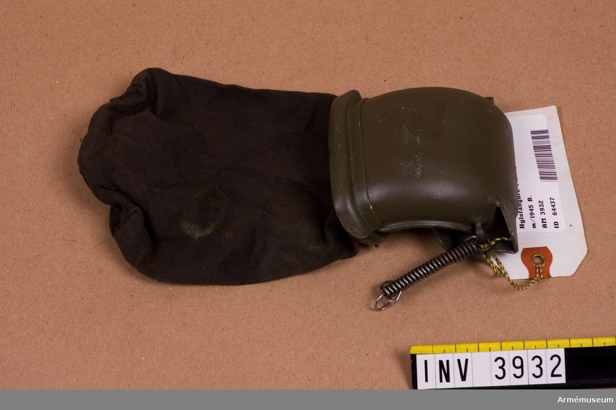 Hylsfångare t kulsprutepistol m/1945 B.Består av: hylsavledare, låsanordning f hylsavledare, hylspåse m låsanordning.Påsen är tillv. av terylen och har kantskoning av vävplast.