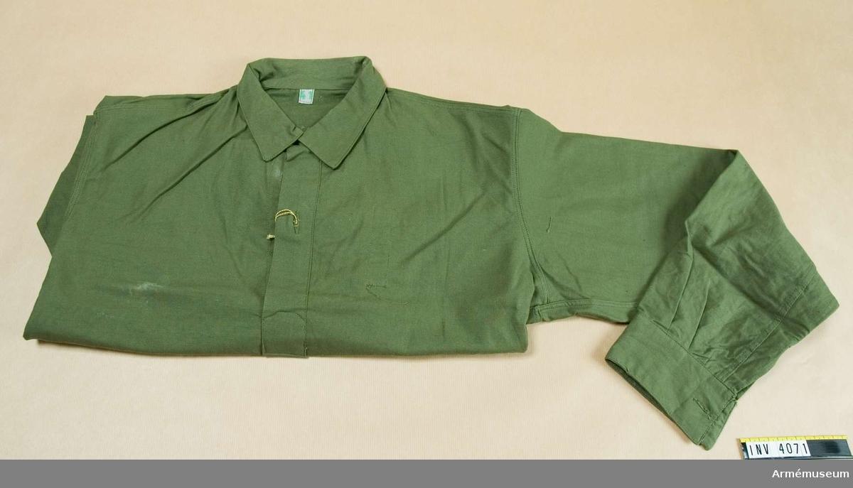 """Skjorta m/1959. Bomullsflanell. Storlek: 41. Skjorta av flanell, grön. Med dubbel fast krage  med halssprund mitt fram knäppt med en nylonknapp. Upptill  under kragen knäpps med hank. Enkel manschett knäppt med en  kanpp. I sidorna rundade slitsar. Nedtill t.v. insidan är  skjortan märkt: """"tre kronor"""" 62 Gefa . Bak i nacken en etikett  märkt: 41."""
