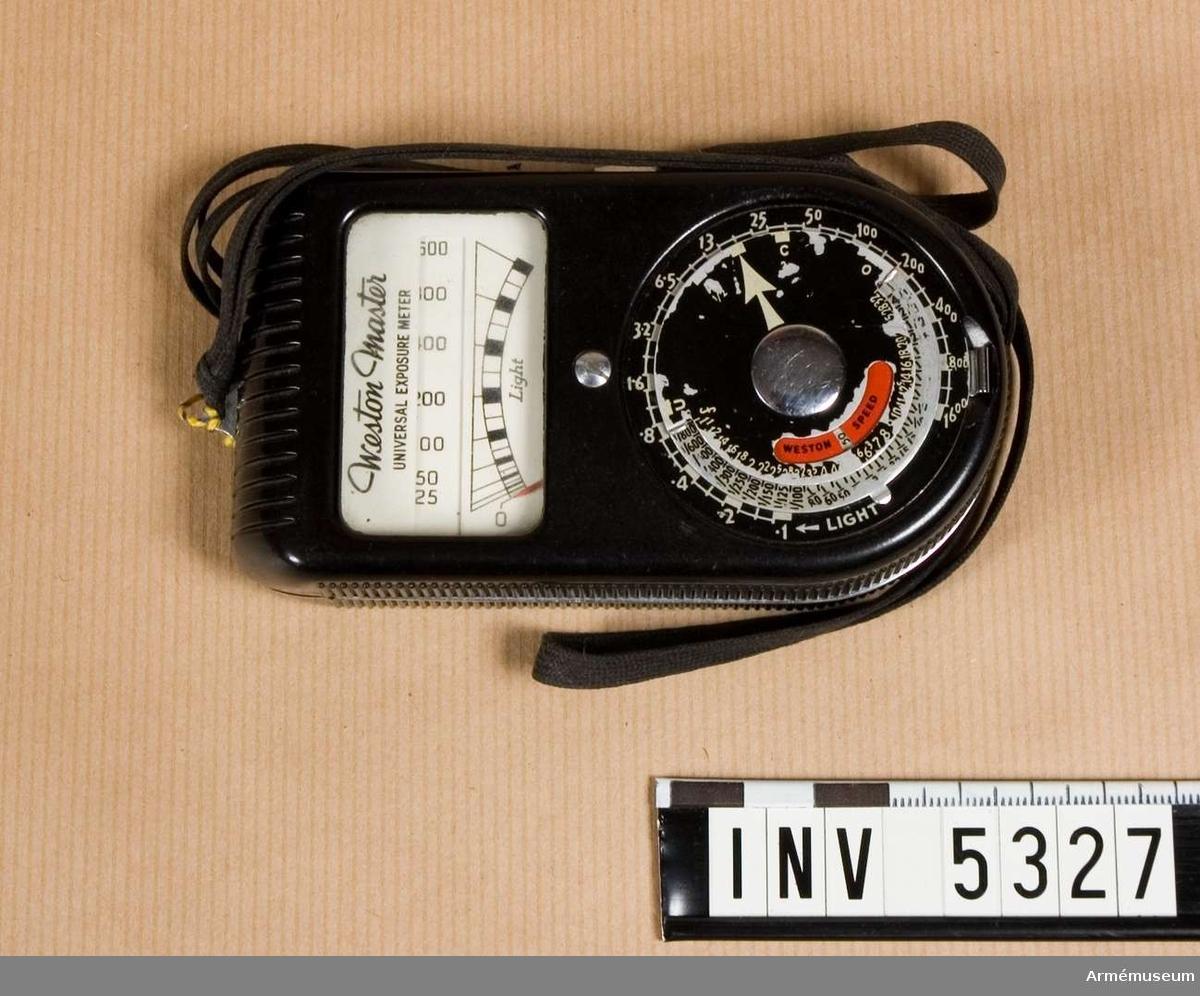 """Föremålet består av instrument och bärsnodd av brunt textilband 2 x 780 mm långt. Färgen är mest svart, texten är vit och skalan för känslighet är röd. Instrumentet är till det yttre i slitet skick, men det fungerar. Tillverkningsnummer A3626.Instrument för mätning av ljus och därpå beräkning av lämpliga värden för kamerans inställning vid fotografering. Användes manuellt. Principen är att en selencell belyses och därvid genererar en elektrisk ström som mätes med ett instrument. Stömmen eller spänningen varierar med belysningen. Det visade värdet omvandlas med mekaniska skalor till värden som kan ställas in på kameran med hänsyn till filmkänsligheten som ställts in på instrumentet.Ordet """"exponeringsmätare"""" är vanligare än det troligen  riktigare """" ljusmätare """"."""