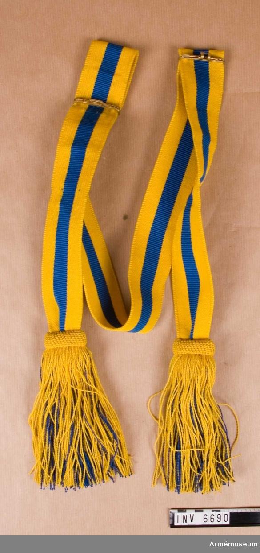 Vävt av redgarn ett tämligen strävt kamgarn  - yllegarn - i två gula ränder diagonalvävt. I mitten en blå rand i ripsväv.  Ganska tunna tofsar i blått och gult.
